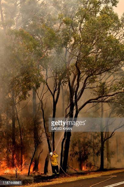 Firefighters conduct backburning measures to secure residential areas from encroaching bushfires in the Central Coast some 90110 kilometres north of...