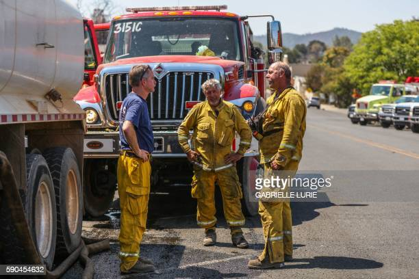 Firefighters confer during a break from aiding in the destruction caused by the Clayton Fire in Lower Lake California August 16 2016 A man was...