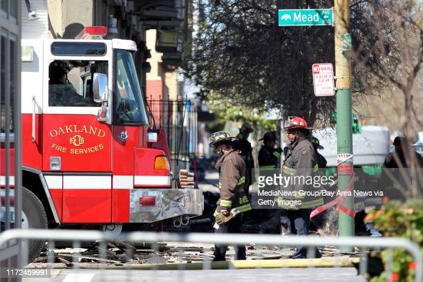 Firefighters continue to remain on scene at a West Oakland residential building gutted by a Monday fatal fouralarm fire along San Pablo Avenue in...