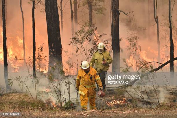Firefighters create a back burn ahead of a fire front in the New South Wales town of Jerrawangala on January 1 2020 A major operation to reach...