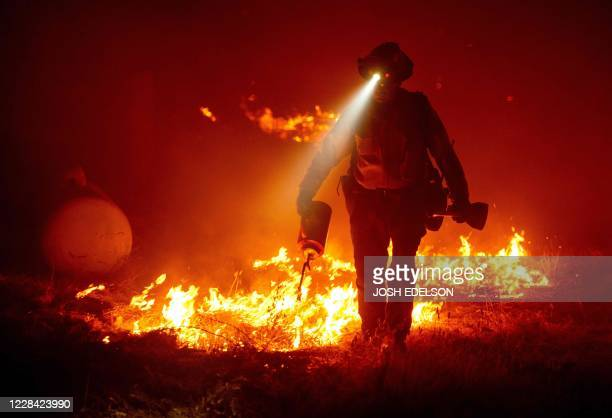 Firefighters cut defensive lines and light backfires to protect structures behind a CalFire fire station during the Bear fire, part of the North...