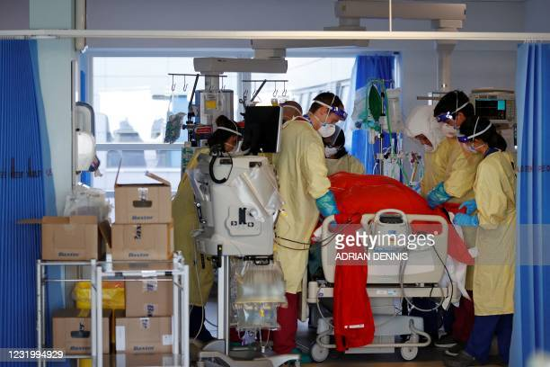 Firefighters Dan Joslin and Matt Smither help prone a Covid-19 patient as they work alongside critical care nurses in the Intensive Care Unit at...