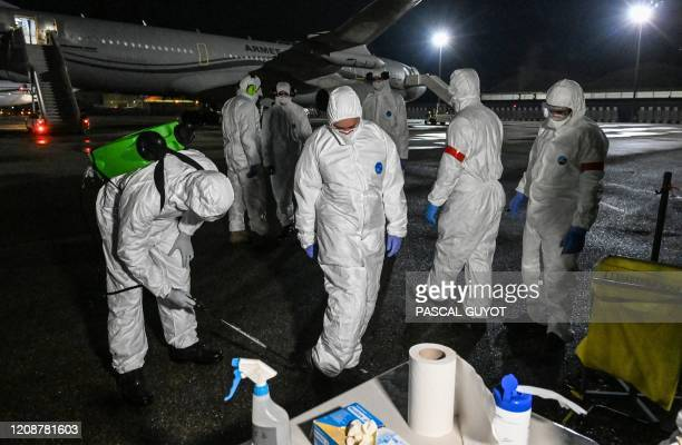 Firefighters decontaminate soldiers stepping out of an Airbus A320 medicalized by the French army upon their arrival from a a mission in Mulhouse on...
