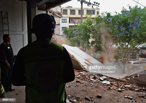 Firefighters demolish a damaged wall after a strong earthquake in Mexico City on May 8 2014 A strong 64magnitude earthquake rattled Mexico on...