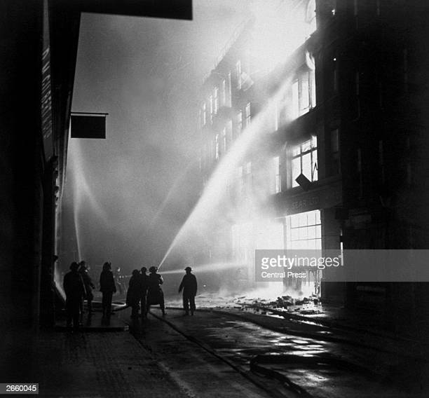 Firefighters direct their hoses onto a blazing building after an incendiary raid on the City of London during the Blitz
