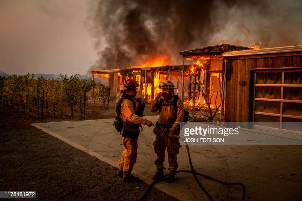 TOPSHOT Firefighters discuss how to approach the scene as a home burns near grape vines during the Kincade fire in Healdsburg California on October...