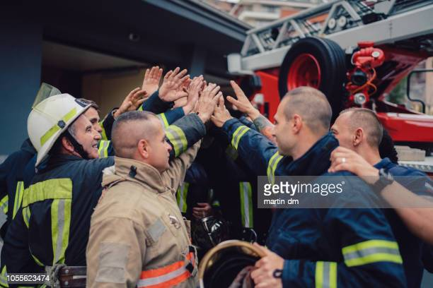 firefighters doing high five - rescue services occupation stock pictures, royalty-free photos & images