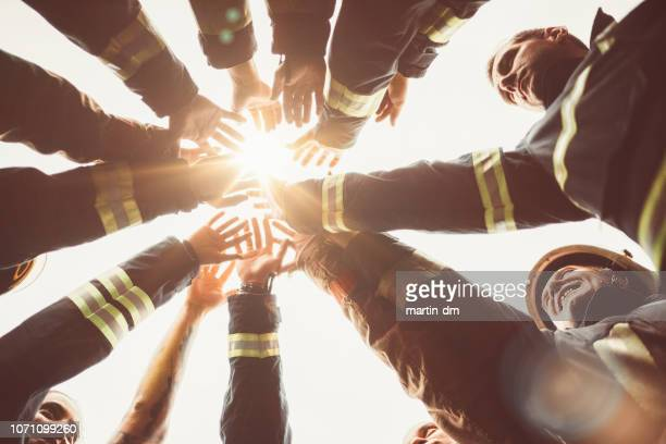 firefighters doing high five - firefighter stock pictures, royalty-free photos & images