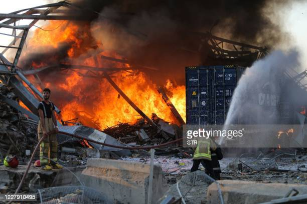 Firefighters douse a blaze at the scene of an explosion at the port of Lebanon's capital Beirut on August 4, 2020. - Two huge explosion rocked the...