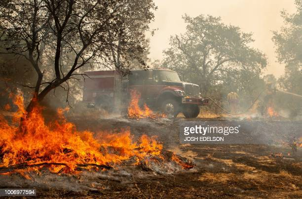 TOPSHOT Firefighters douse a hotspot near various homes as the Carr fire continues to burn near Redding California on July 28 2018 The US federal...