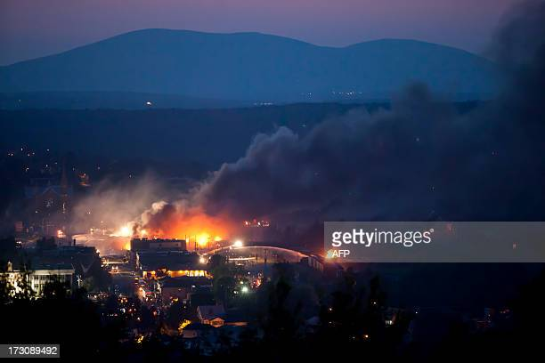 Firefighters douse blazes after a freight train loaded with oil derailed in Lac-Megantic in Canada's Quebec province on July 6 sparking explosions...