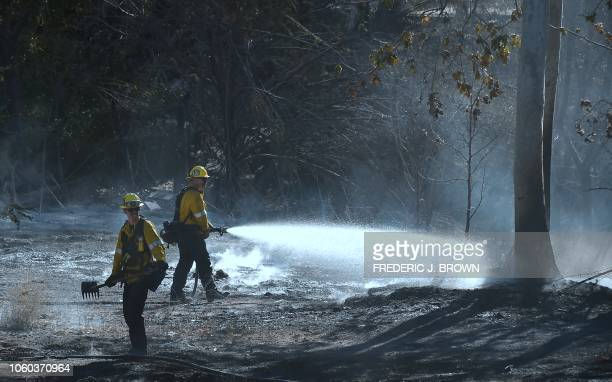 Firefighters douse burning embers off Kanan Dume Road a canyon road which cuts across the mountains to Malibu California on November 11 as the battle...
