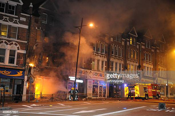 firefighters douse fire after london riots - riot stock pictures, royalty-free photos & images