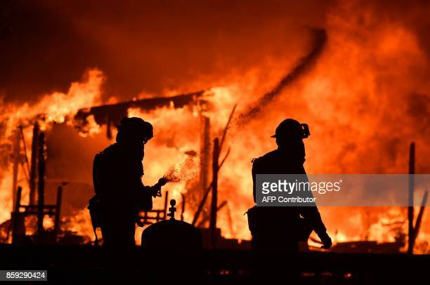 Firefighters douse flames as a home burns in the Napa wine region in California on October 9 as multiple winddriven fires continue to whip through...