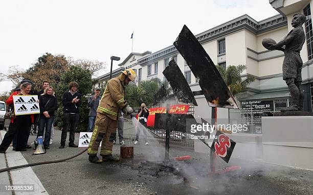 Firefighters douse flames as the Adidas logo is set alight at Eden Park on August 13 2011 in Auckland New Zealand Anticapitalist group Socialist...
