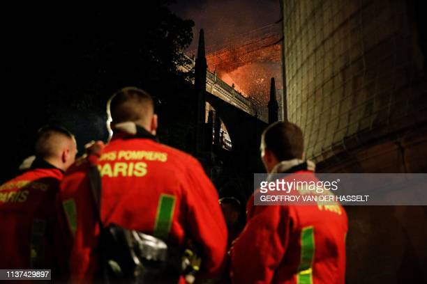 Firefighters douse flames billowing from the roof at NotreDame Cathedral in Paris on April 15 2019 A fire broke out at the landmark NotreDame...