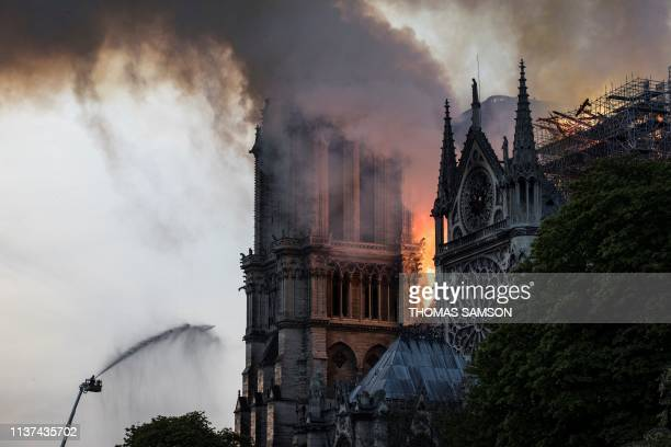 TOPSHOT Firefighters douse flames billowing from the roof at NotreDame Cathedral in Paris on April 15 2019 A huge fire swept through the roof of the...