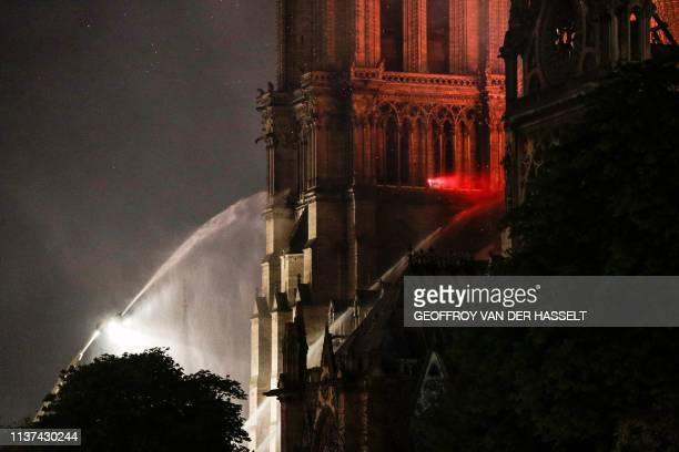 Firefighters douse flames rising from the roof at NotreDame Cathedral in Paris on April 15 2019 A fire broke out at the landmark NotreDame Cathedral...