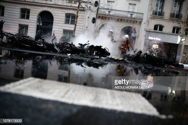 TOPSHOT Firefighters douse the flames of burning motorcycles in Paris on January 5 which were set alight during an antigovernment demonstration...