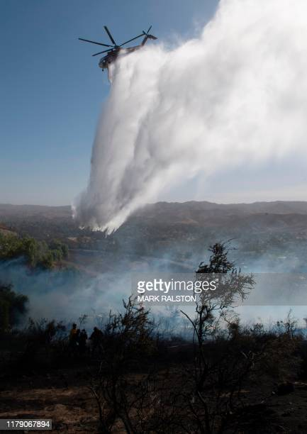 Firefighters drop water on the area near to the Reagan Library during the Easy Fire in Simi Valley California on October 30 2019 Firefighters in...