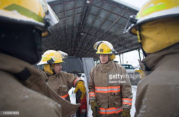 firefighters encircle another firefighter who is talking