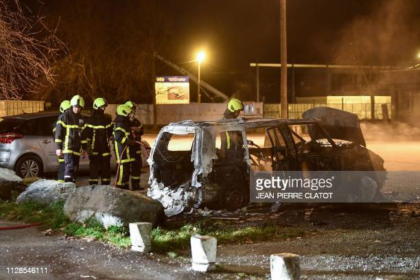 Firefighters extinguish a car set on fire in the street where riots sparked on March 3 2019 following the death of 2 young people on a scooter as...