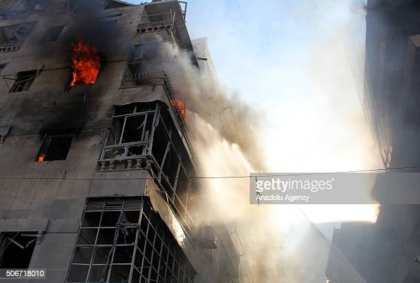 Firefighters extinguish a fire after Daesh terrorists' carbomb attack against Ahrar ashSham Headquarters in Aleppo Syria on January 25 2016Car bomb...
