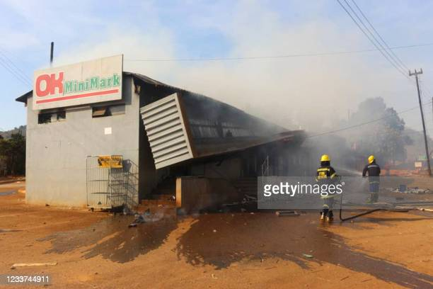 Firefighters extinguish a fire at a supermarket in Manzini, Eswatini, on June 30, 2021. - Demonstrations escalated radically in Eswatini this week as...