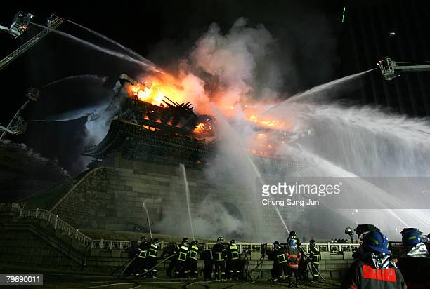 Firefighters extinguish a fire at Namdaemun which is South Korea's Number One national treasure on February 11 2008 in Seoul South Korea The...