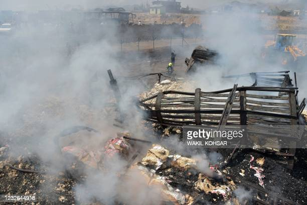 Firefighters extinguish a fire following an overnight ablaze in which several fuel tankers caught fire at Qala-e-Murad Bek area on the outskirts of...