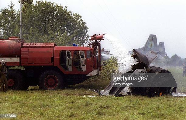 Firefighters extinguish a fire in the wreckage of a Su-27 fighter jet that crashed into a huge crowd of spectators at an air show in Lviv, Ukraine,...