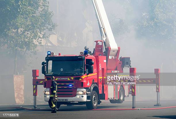Firefighters extinguish a fire which ravaged the construction site of the Hotel de BourbonConde on August 21 2013 in Paris France The hotel was in...