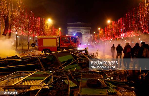 TOPSHOT Firefighters extinguish burning material near The Arc de Triomphe on the Champs Elysees in Paris on November 24 during a rally by yellow vest...