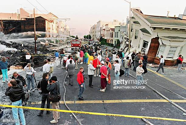 Firefighters extinguish fire in the Marina District in San Francisco 21 October 989 after a quake erupted 17 October in the city, killing an...