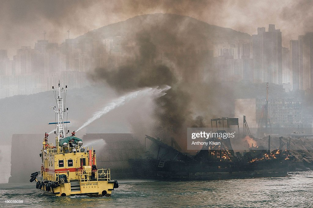 Firefighters extinguish fires on boats at the Shau Kei Wan typhoon shelter on September 27, 2015 in Hong Kong. A fire swept through several boats anchored at the Shau Kei Wan typhoon shelter.