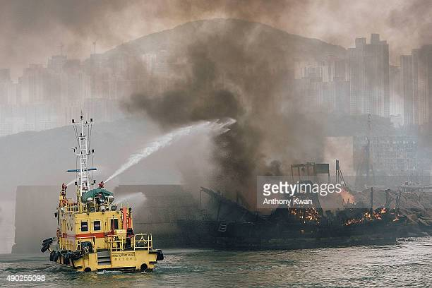 Firefighters extinguish fires on boats at the Shau Kei Wan typhoon shelter on September 27 2015 in Hong Kong A fire swept through several boats...