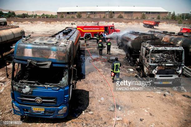 Firefighters extinguish fuel tankers that went on fire at a lorry park near Iran's western city of Kermanshah on July 28, 2020. - The blaze sent up a...