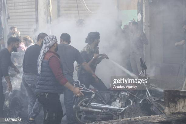 Firefighters extinguish the burning vehicles at the scene after the attacks came from two bombladen vehicles in alBab district in Syria on November...