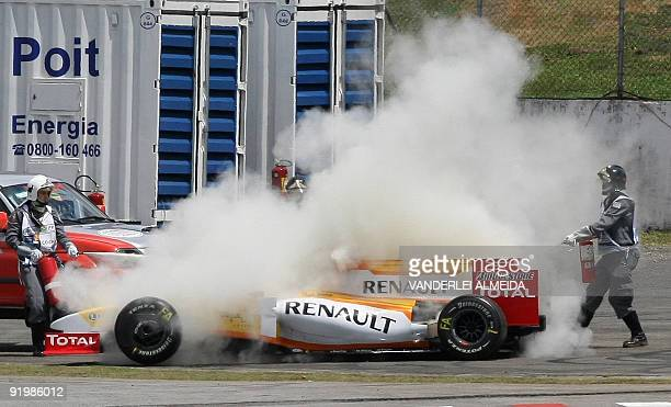 Firefighters extinguish the car of Spanish Fernando Alonso of Renault after a crash during Brazilian Formula one Grand Prix at the Interlagos race...