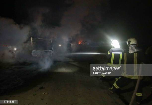 Firefighters extinguish the flames of a burning truck at the spot where Abu Hassan alMuhajir the Islamic State group's spokesman was reportedly...