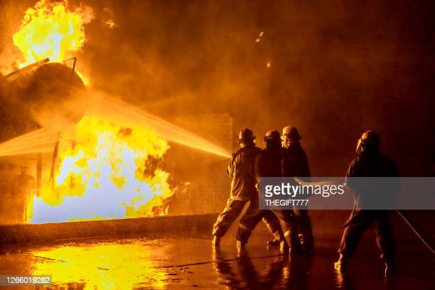firefighters extinguishing an industrial fire - firefighter stock pictures, royalty-free photos & images