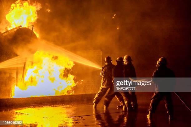 産業火災を消火する消防士 - 消防士 ストックフォトと画像