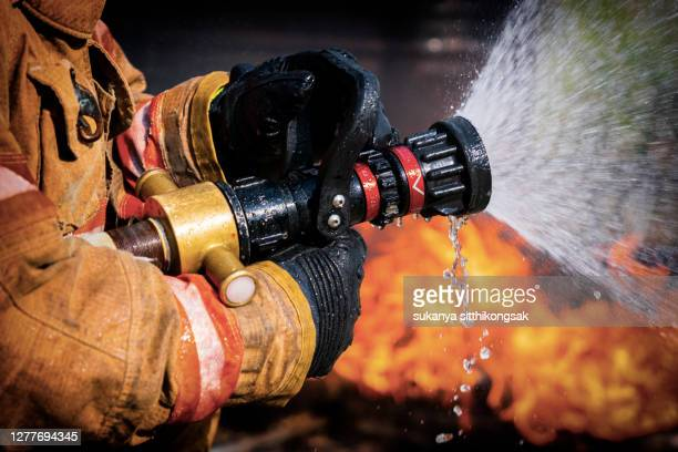 firefighters extinguishing house fire. - burning stock pictures, royalty-free photos & images