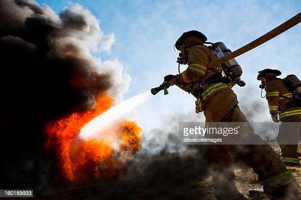 firefighters extinguishing house fire - rescue worker stock pictures, royalty-free photos & images
