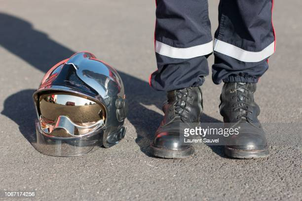 firefighter's feet and helmet - frankreich stock-fotos und bilder
