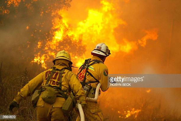 Firefighters fight back blazes along 118 freeway 27 October 2003 in Simi Valley CA 35 miles northwest of Los Angeles Firefighters were working to...