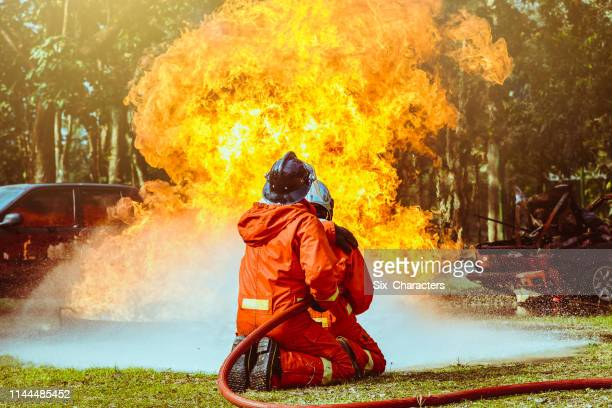 firefighters fighting a fire operation, water spray by high pressure nozzle to fire surround with smoke, firefighters extinguish a house - extinguishing stock pictures, royalty-free photos & images