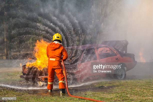 firefighters fighting a fire operation, water spray by high pressure nozzle to fire surround with smoke, firefighters extinguish a car - in flames i the mask stock pictures, royalty-free photos & images