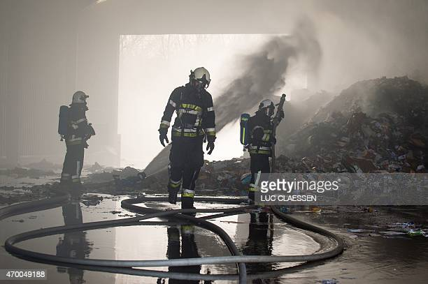 Firefighters finish to extinguish a blaze that broke out at a warehouse of IOK Afvalbeheer stocking paper company on April 17 2015 in Meerhout east...