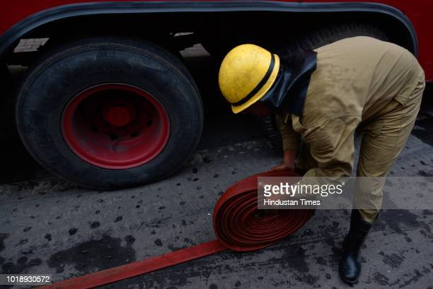 Firefighters folding the hoze pipe after dozing a fire inside the office of Enforcement Directorate on sixth floor at Lok Nayak Bhawan Khan Market on...